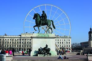 Vue sur la statue de Louis XIV sur son cheval au centre de la place et en arriere plan on peut apercevoir la grande roue à Lyon, place Bellecour